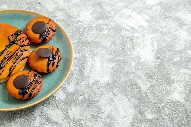 Widok z przodu pyszne ciasta kakaowe z polewą czekoladową wewnątrz talerza na białym tle słodkie ciasto herbatniki deserowe ciasteczka