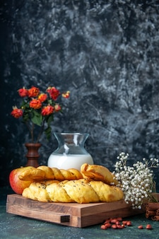 Widok z przodu pyszne ciasta z mąką i mlekiem na ciemnej ścianie ciasto ciasto hotcake słodka bułka deser ciasto cukier