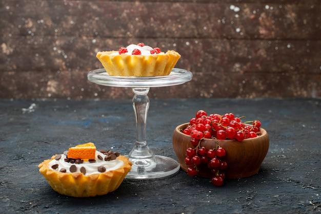 Widok z przodu pyszne ciasta ze śmietaną i owocami na ciemnej powierzchni słodkie jagody