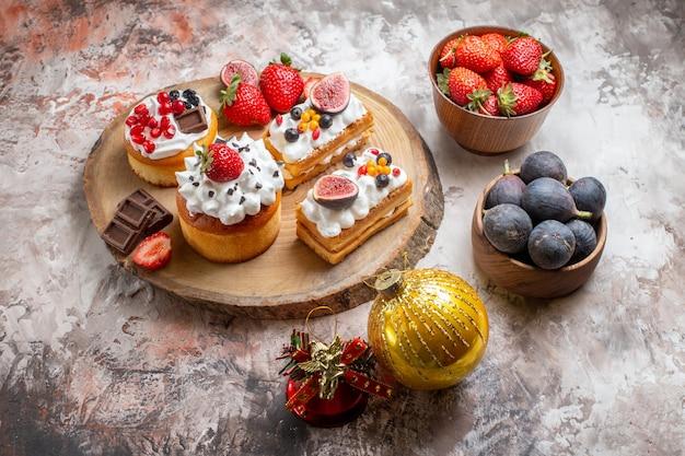 Widok z przodu pyszne ciasta ze świeżymi owocami na jasnym tle świąteczne ciastka deserowe kolorowe ciastka