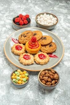 Widok z przodu pyszne ciasteczka piaskowe z ciasteczkami i cukierkami na białej przestrzeni