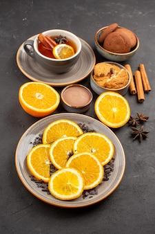 Widok z przodu pyszne ciasteczka piaskowe ze świeżymi pokrojonymi pomarańczami i filiżanką herbaty na ciemnym tle ciastko z cukrem słodkie ciasteczka owocowe