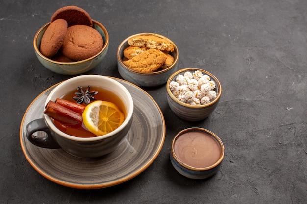 Widok z przodu pyszne ciasteczka z filiżanką herbaty na ciemnym tle ciastko z cukrem ciastko deserowe słodkie