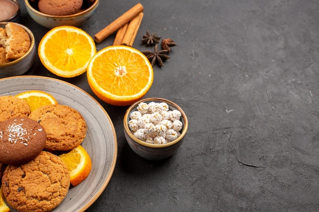 Widok z przodu pyszne ciasteczka z piasku ze świeżymi pokrojonymi pomarańczami na ciemnym tle herbatniki owocowe słodkie ciasteczka cukier cytrusowy