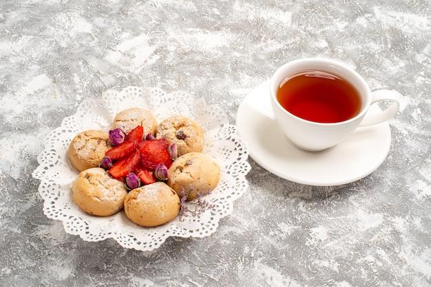 Widok z przodu pyszne ciasteczka z piasku ze świeżymi truskawkami i filiżanką herbaty na białej przestrzeni