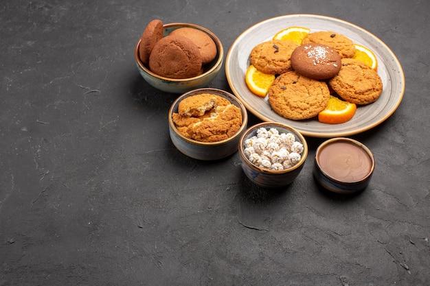 Widok z przodu pyszne ciasteczka ze świeżymi pokrojonymi pomarańczami na ciemnej podłodze herbatniki owocowe słodkie ciasteczka cytrusowe
