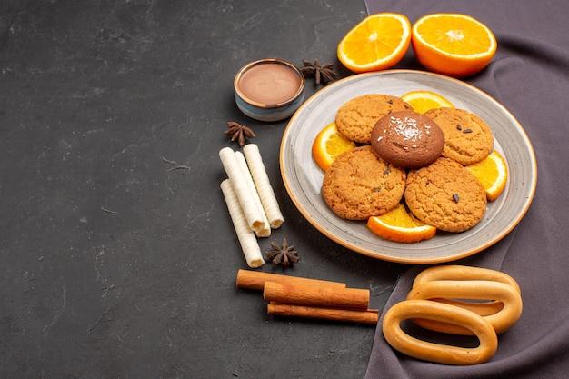 Widok z przodu pyszne ciasteczka ze świeżymi pokrojonymi pomarańczami na ciemnym tle ciastko z cukrem ciastko owocowe słodkie