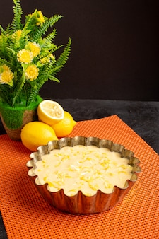 Widok z przodu pyszne ciasto cytrynowe kwaśne pyszne egzotyczne ciasto piekarnicze słodkie na ciemnym biurku