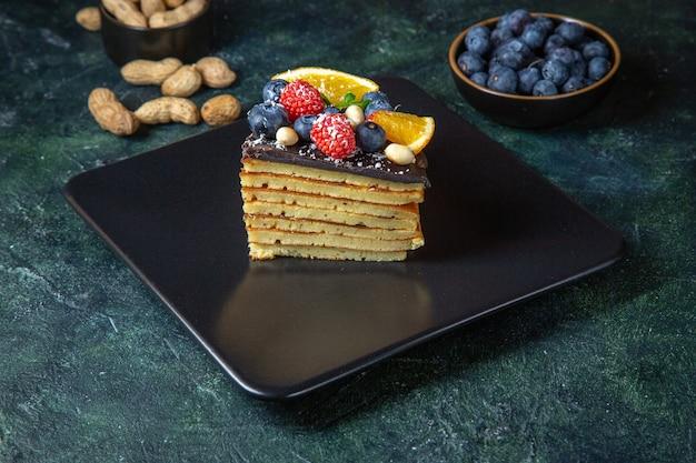 Widok z przodu pyszne ciasto czekoladowe z owocami na ciemnej ścianie