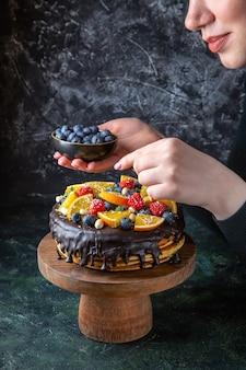 Widok z przodu pyszne ciasto czekoladowe zdobione owocami przez kobietę na ciemnej ścianie