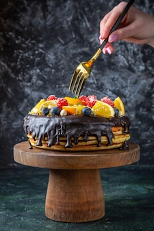 Widok z przodu pyszne ciasto czekoladowe ze świeżymi owocami na ciemnej ścianie