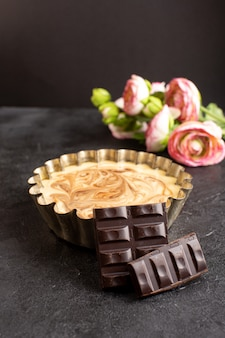 Widok z przodu pyszne ciasto kawowe słodka czekolada pyszne cukier piekarnia ciasto słodkie wraz z różami na ciemnym biurku