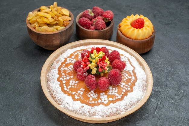 Widok z przodu pyszne ciasto malinowe z rodzynkami na szarym tle cukier herbata herbatniki ciasto ciastko słodkie ciasto