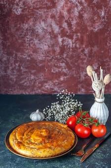 Widok z przodu pyszne ciasto mięsne wewnątrz patelni z pomidorami na ciemnym tle jedzenie piec ciasto ciastko ciasto kolor piekarnika