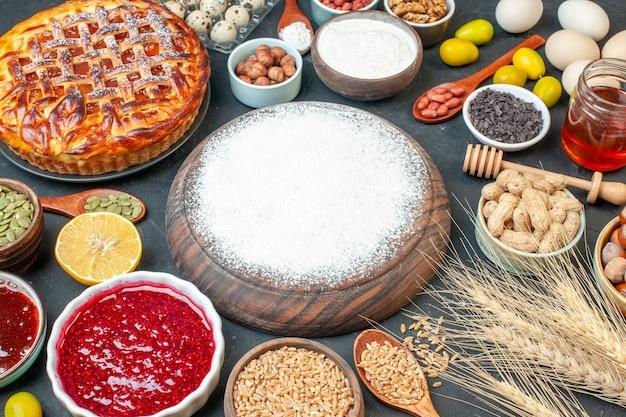 Widok z przodu pyszne ciasto owocowe z orzechami mąki i dżemem na ciemnym stole