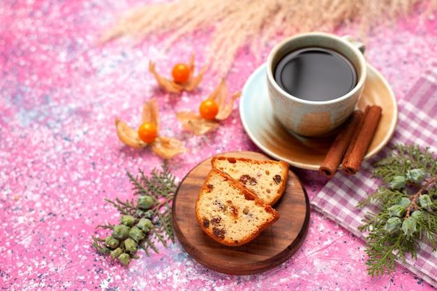 Widok z przodu pyszne ciasto pokrojone w plasterki z filiżanką herbaty i cynamonem na różowym biurku.