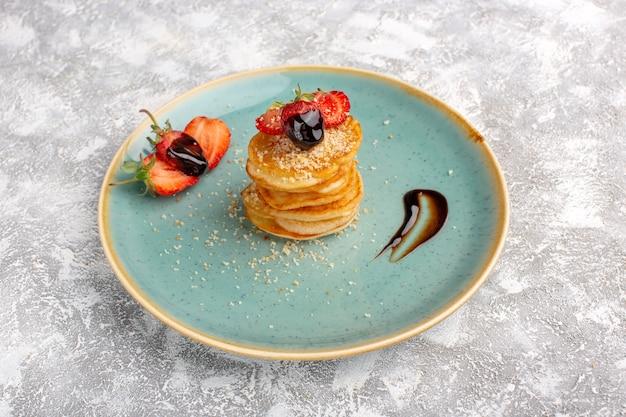 Widok z przodu pyszne ciasto słodkie z truskawkami wewnątrz talerza na białym stole, słodkie ciasto cukrowe do pieczenia
