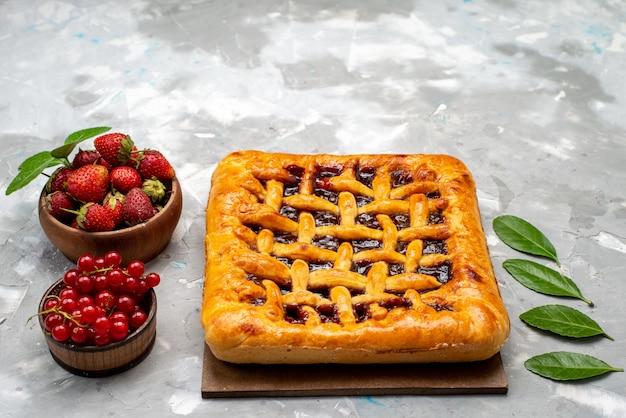 Widok z przodu pyszne ciasto truskawkowe z galaretką truskawkową w środku wraz ze świeżymi truskawkami i żurawiną na szarym biurku