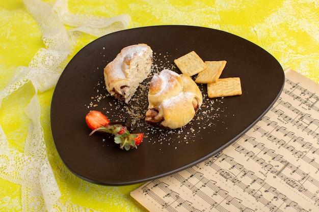 Widok z przodu pyszne ciasto wewnątrz brązowego talerza z krakersami na żółtym stole, upiecz słodkie ciasto owocowe z herbatą