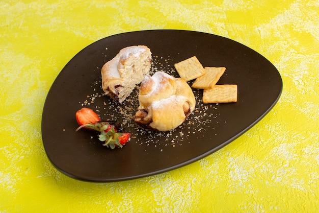 Widok z przodu pyszne ciasto wewnątrz talerza z krakersami na żółtym stole, upiec słodkie ciasto owocowe z herbatą
