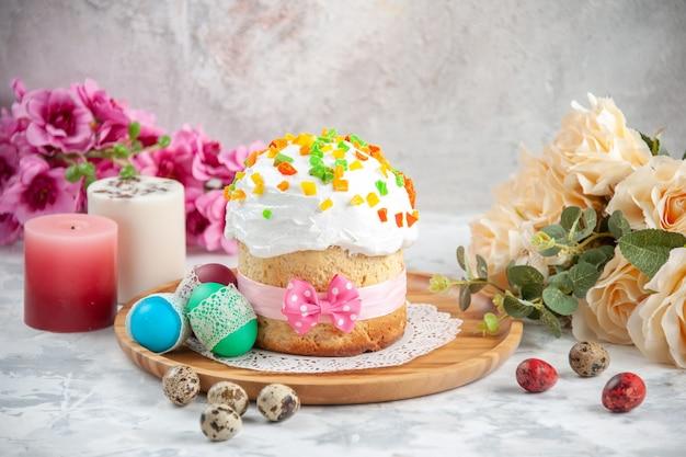 Widok z przodu pyszne ciasto wielkanocne z suszonymi owocami i kolorowymi jajkami na białym tle koncepcja wiosenny kolorowy ozdobny ciasto deserowe kolor