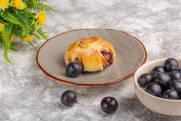 Widok z przodu pyszne ciasto z nadzieniem wraz z tarniną na lekkim stole, słodkie ciasto cukrowe upiec ciasto owocowe