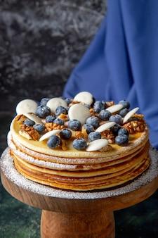 Widok z przodu pyszne ciasto z orzechami włoskimi, jagodami i ciasteczkami o ciemnej powierzchni