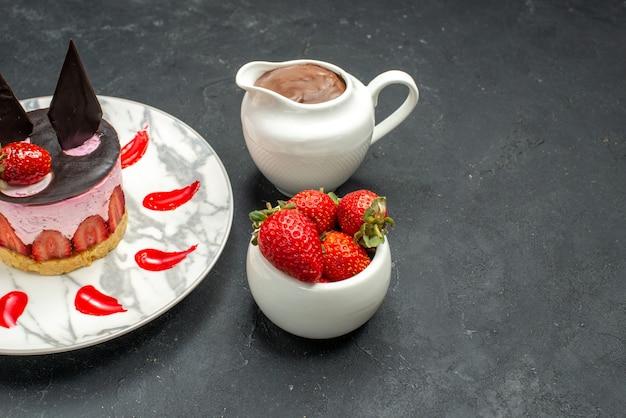 Widok z przodu pyszne ciasto z truskawkami i czekoladą na owalnym talerzu miska truskawek