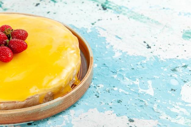 Widok z przodu pyszne ciasto z żółtym syropem i świeżymi czerwonymi truskawkami na jasnoniebieskiej powierzchni