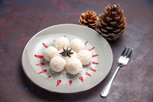 Widok z przodu pyszne cukierki kokosowe małe i okrągłe uformowane wewnątrz talerza na ciemnej przestrzeni