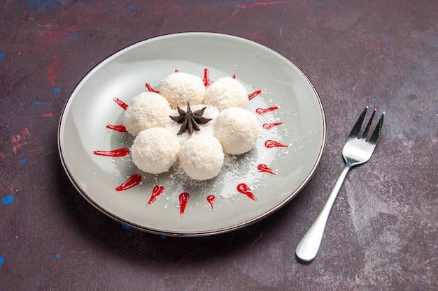 Widok z przodu pyszne cukierki kokosowe okrągłe uformowane z czerwonym lukrem na ciemnej przestrzeni