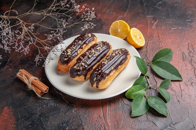 Widok z przodu pyszne czekoladowe eklery wewnątrz talerza na ciemnym tle