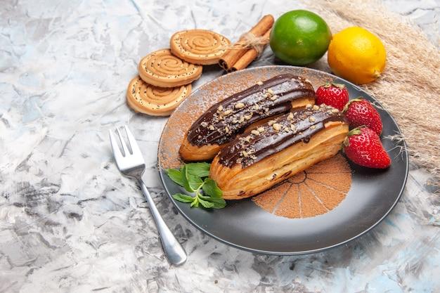 Widok z przodu pyszne czekoladowe eklery z ciasteczkami na jasnym ciastku deserowym