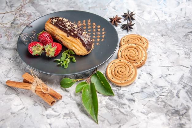Widok z przodu pyszne czekoladowe eklery z ciasteczkami na jasnym deserze z ciasta biszkoptowego