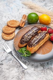 Widok z przodu pyszne czekoladowe eklery z ciasteczkami na jasnym stole z ciastem deserowym