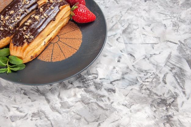 Widok z przodu pyszne czekoladowe eklery z truskawkami na jasnej podłodze ciastko deserowe