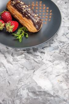 Widok z przodu pyszne czekoladowe eklery z truskawkami na jasnej podłodze z cukierków deserowych