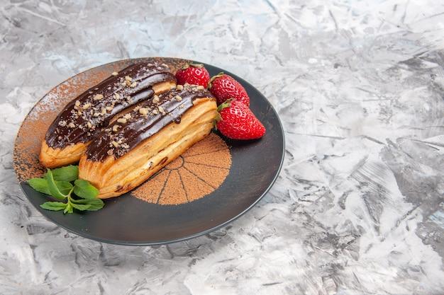 Widok z przodu pyszne czekoladowe eklery z truskawkami na jasnym ciastku deserowym na biurko