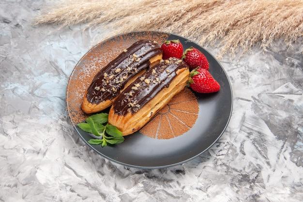 Widok z przodu pyszne czekoladowe eklery z truskawkami na jasnym deserze ciasteczka biszkoptowe