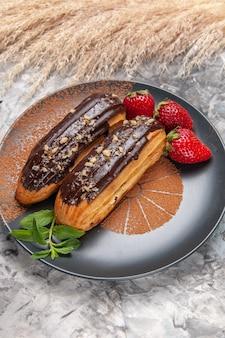 Widok z przodu pyszne czekoladowe eklery z truskawkami na jasnym deserze z ciastek na stole
