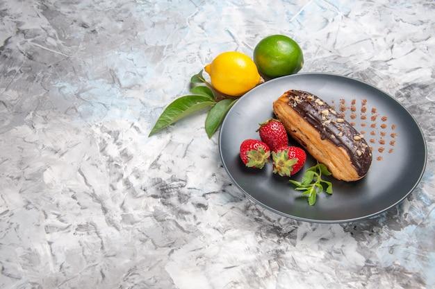 Widok z przodu pyszne czekoladowe eklery z truskawkami na jasnym stole deserowym z cukierkami