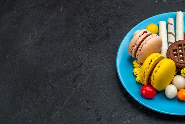 Widok z przodu pyszne francuskie macarons z cukierkami i czekoladowymi ciasteczkami na szarym biurku biszkoptowe ciasto cukrowe słodkie ciasteczko do pieczenia