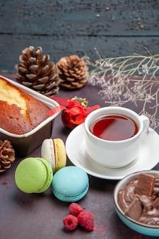 Widok z przodu pyszne francuskie makaroniki z czekoladą i filiżanką herbaty na ciemnym tle napój herbaciany ciasto biszkoptowe ciastko