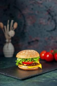 Widok z przodu pyszne hamburger mięsny z czerwonymi pomidorami na ciemnym tle