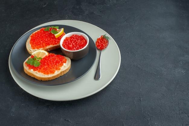 Widok z przodu pyszne kanapki z kawiorem wewnątrz talerza na ciemnym tle posiłek tostowy chleb obiad danie przekąska śniadanie jedzenie
