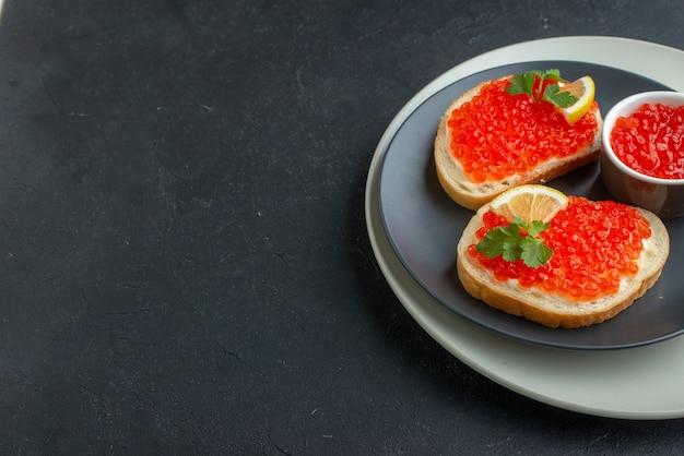Widok z przodu pyszne kanapki z kawiorem wewnątrz talerza na ciemnym tle tosty mączka rybna chleb danie przekąska śniadanie jedzenie