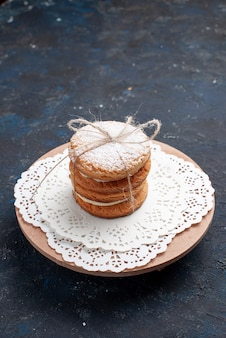Widok z przodu pyszne kanapkowe ciasteczka zawiązane pyszne na granatowym torcie na biurku