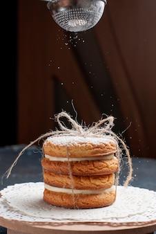 Widok z przodu pyszne kanapkowe ciasteczka zawiązane pyszne zdobywanie cukru pudru na granatowym torcie na biurku