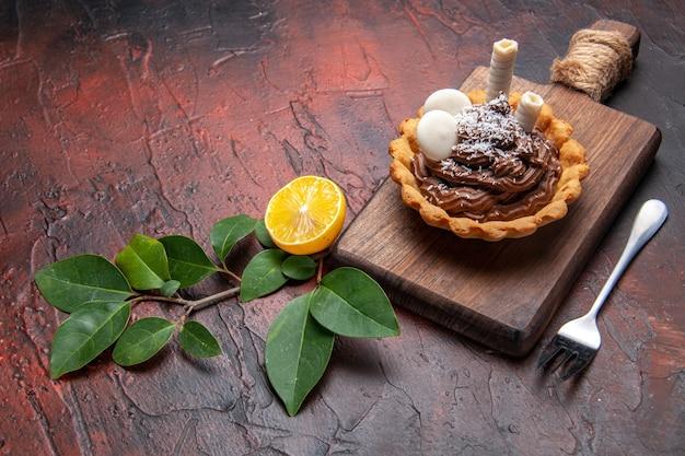 Widok z przodu pyszne kremowe ciasto na ciemnym stole ciasto biszkoptowe deser słodki