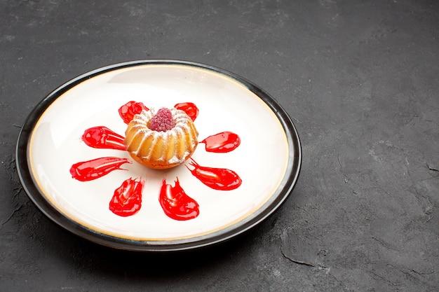 Widok z przodu pyszne małe ciasto z czerwonym lukrem wewnątrz talerza na ciemnym tle herbata słodkie ciasteczka ciasteczka cukier